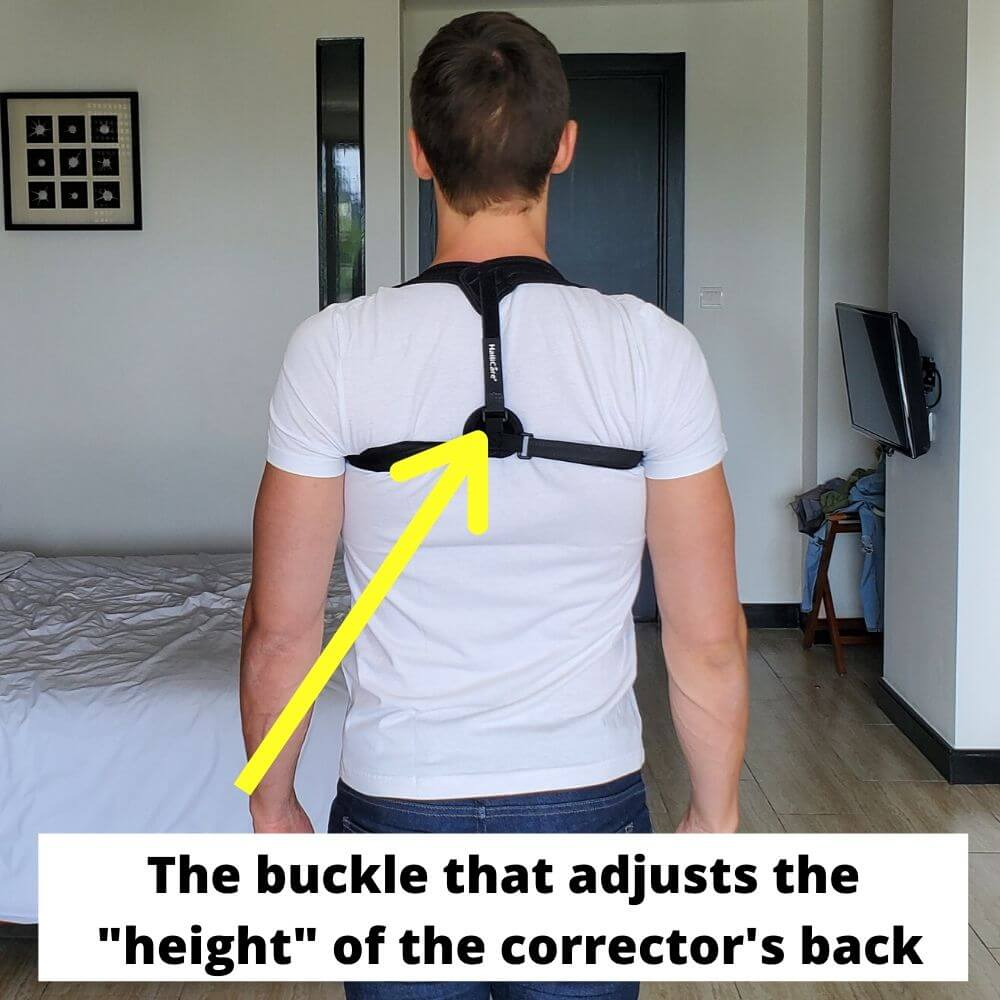 a young man standing with one of the posture braces on his back